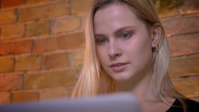 特写镜头画象年轻俏丽金发女性千福年键入在膝上型计算机和坐长沙发户内 股票录像