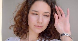 特写镜头画象年轻逗人喜爱的长发卷曲白种人女性式样微笑愉快地看的照相机与 影视素材