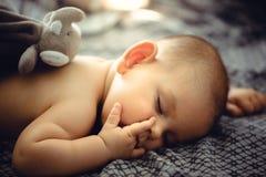 特写镜头画象睡觉在尿布无罪的灰色床上 库存图片