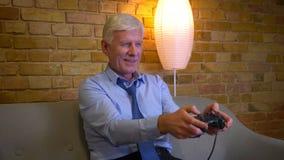 特写镜头画象老白种人businessmanplaying的电子游戏和赢得是在长沙发的愉快的开会户内  影视素材