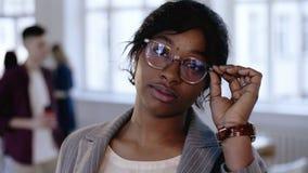 特写镜头画象,接触镜片的专业年轻非洲教练女商人,看照相机在办公室 股票视频