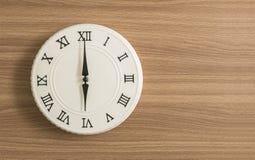 特写镜头白色时钟为在6个o在木书桌被构造的背景的`时钟装饰与拷贝空间 库存照片