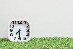 特写镜头白色时钟为装饰展示一个一半通过七或7:30 a M 在绿色人为草地板和被构造的奶油墙纸上 免版税库存照片