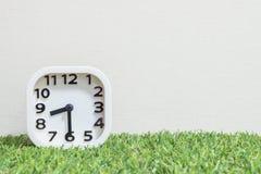 特写镜头白色时钟为装饰展示一个一半通过八或8:30 a M 在绿色人为草地板和被构造的奶油墙纸上 库存照片