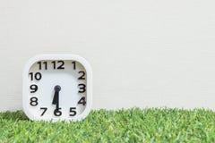 特写镜头白色时钟为装饰展示一个一半通过六或6:30 a M 在绿色人为草地板和奶油墙纸构造了ba 免版税库存图片