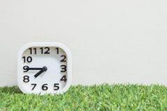 特写镜头白色时钟为装饰展示每处所到八或7:45 a M 在绿色人为草地板和被构造的奶油墙纸上 免版税库存图片