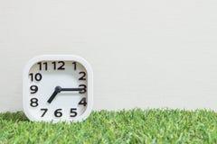 特写镜头白色时钟为装饰展示每处所通过七或7:15 a M 在绿色人为草地板和奶油墙纸textur上 库存照片