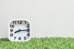 特写镜头白色时钟为装饰展示每处所通过八或8:15 a M 在绿色人为草地板和奶油墙纸textur上 库存图片
