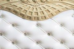 特写镜头白色织品布置了床头板有按钮纺织品背景,减速火箭的时髦的卧室家具 免版税图库摄影