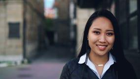 特写镜头看与愉快的微笑的可爱的亚裔女孩慢动作画象照相机站立在街道佩带 影视素材