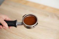 特写镜头碾碎的咖啡紧紧猛撞入咖啡机的持有人 免版税库存照片