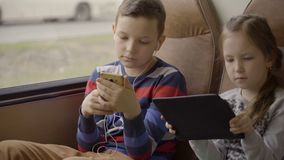 特写镜头移动乘公共汽车的射击了一个年轻男孩和女孩穿过城市,使用社会网络在他们的小配件 股票视频