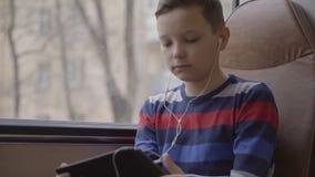 特写镜头移动乘公共汽车的射击了一个年轻男孩穿过城市,使用在他的计算机片剂的社会网络 股票视频