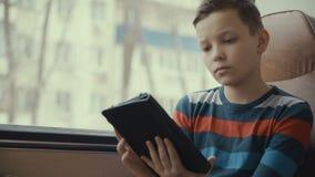 特写镜头移动乘公共汽车的射击了一个年轻男孩穿过城市,使用在他的计算机片剂的社会网络 影视素材