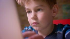 特写镜头移动式摄影车被射击逗人喜爱的小男孩与在家被集中的膝上型计算机一起使用 影视素材
