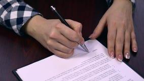 特写镜头签署一个纸张文件或合同-假署名的页的射击了女实业家 股票视频