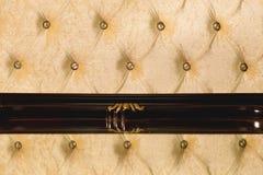 特写镜头米黄织品布置了床头板有按钮纺织品背景,减速火箭的时髦的卧室家具与 免版税库存照片