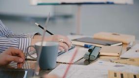 特写镜头繁忙的公司公司工作者在与设备和咖啡的办公室桌后坐在职员会议合作 股票录像