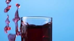 特写镜头红色莓果汁涌入在蓝色背景的一个玻璃杯子 股票视频