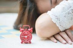 特写镜头红色闹钟软的焦点有被弄脏的睡觉的妇女的大理石书桌背景的,亚洲妇女概念的放松 免版税库存照片