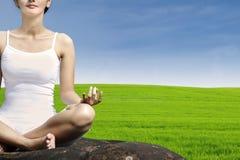 特写镜头绿色领域的瑜伽妇女 免版税库存图片