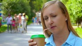 特写镜头美丽的中年妇女饮用的咖啡在夏天公园 股票视频