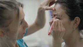特写镜头美容师在一个美丽的客户的眼眉附近指示红色等高 影视素材