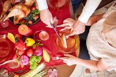 特写镜头老人服务烤了在桌背景的火鸡 感恩晚餐 传统欢乐食物概念 免版税库存照片
