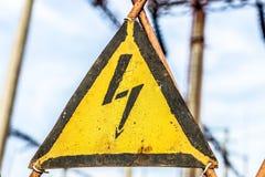 特写镜头老年迈的生锈的三角金属片与高压警报信号 与变压器和电分配的发电站 库存照片