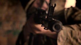 特写镜头聚焦了军事男性藏品自动炮被指挥在照相机,站立平直,没有行动,棕色背景 影视素材