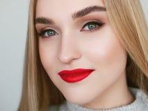 特写镜头自然光微笑的白肤金发的妇女模型,颧骨秀丽画象与充满活力的饱和的红色嘴唇明亮的嘴唇构成的 免版税库存照片
