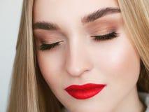 特写镜头自然光白肤金发的妇女模型,颧骨秀丽画象与充满活力的饱和的红色嘴唇明亮的嘴唇构成的和 库存图片