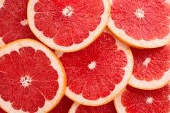 特写镜头葡萄柚切在居住的珊瑚颜色的抽象背景 免版税库存照片