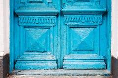 特写镜头蓝色的元素许多次绘了上个世纪的破裂的双管的木葡萄酒门与a的 免版税图库摄影