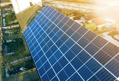 特写镜头表面点燃由在大厦屋顶的太阳蓝色发光的太阳照片流电盘区系统 可更新的生态绿色能量 免版税库存照片