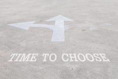 特写镜头表面老和苍白白色绘了在水泥街道地板上的箭头标志与时刻选择词被构造的背景 免版税库存照片