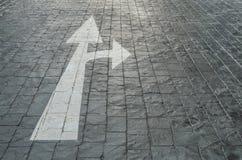 特写镜头表面老和苍白白色绘了箭头签字前进或在黑砖石头地板上的右边在停车场tex 库存图片