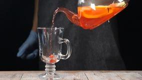 特写镜头被射击倾吐在透明茶壶外面的果子茶入在慢动作的一块玻璃 HD 股票录像