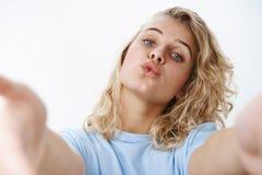 特写镜头被射击傻和女性无忧无虑白肤金发与在T恤杉折叠的嘴唇的蓝眼睛在拉扯手往的亲吻 免版税库存图片