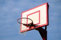 特写镜头被射击在一多云天空蔚蓝的背景的篮球圆环 库存图片