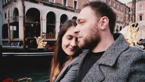 特写镜头被射击在享受威尼斯运河游览游览的长平底船的愉快的年轻激动的白种人新婚佳偶夫妇在意大利 股票录像