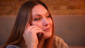 特写镜头被射击轻松的正大小长发模型谈话在有姿势的智能手机在舒适家 影视素材
