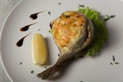 特写镜头被烘烤的鳟鱼服务用沙拉、柠檬和调味汁 库存照片