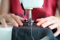 特写镜头裁缝递在家工作在缝纫机 缝合的过程 在缝合的特写镜头后的妇女手 免版税图库摄影