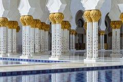 特写镜头装饰了在上面的大理石柱与象有被反射的水池的金黄棕榈在扎耶德Grand Mosque回教族长前面 库存图片