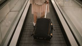 特写镜头观点的带着站立在自动扶梯的手提箱的少妇在机场 女性行家准备对去绊倒 免版税库存照片