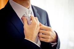 特写镜头观点的新郎在婚礼前递改正领巾 免版税库存图片