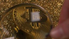 特写镜头视图通过在Bitcoin模型的寸镜反对光线 股票录像