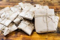 特写镜头许多礼物包裹了在木背景的牛皮纸 一个大礼物 免版税库存照片