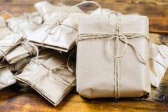 特写镜头许多礼物包裹了在木背景的牛皮纸 一张大当前正面图 免版税库存照片